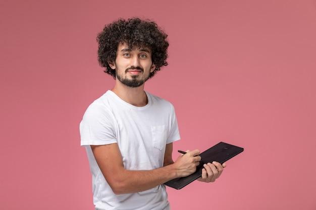ノートブックにいくつかのメモを取る正面図の若い男