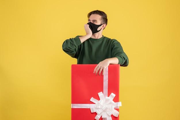 Giovane di vista frontale che pensa a qualcosa che sta dietro il grande giftbox su giallo