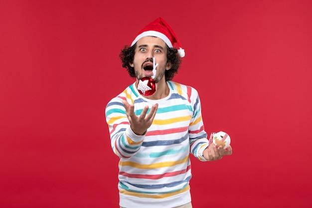 빨간 벽에 크리스마스 트리 장난감을 던지는 전면보기 젊은 남자 휴일 빨간색 인간의 새 해