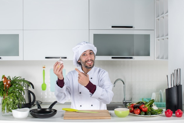 Front view young man in uniform pointing at garlic in kitchen