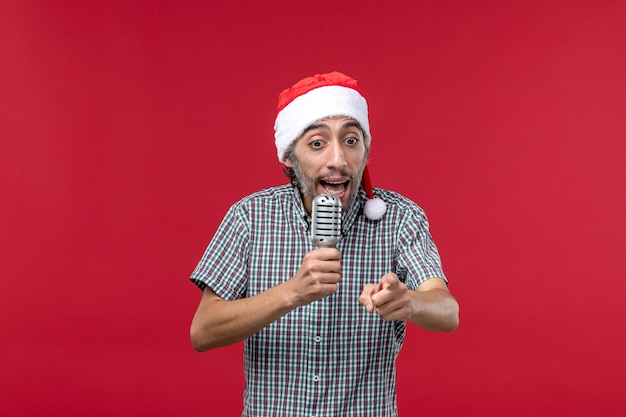 Front view young man using microphone on red wall emotion holiday singer music