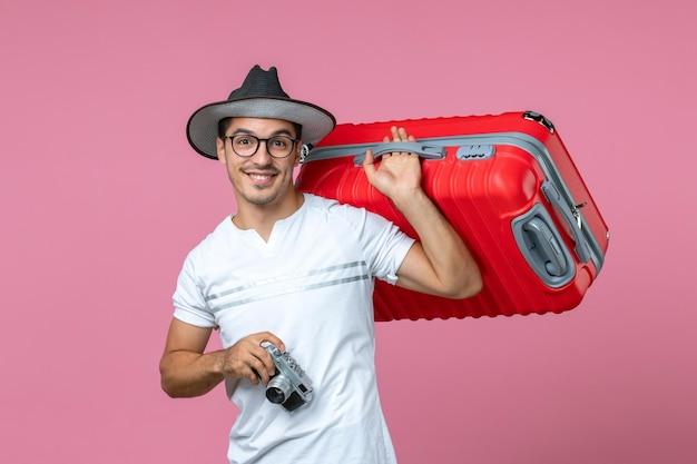 Vista frontale di un giovane in vacanza che scatta foto con una borsa rossa sul muro rosa