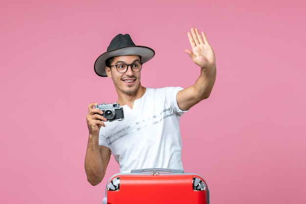 Front view of young man in vacation with bag holding camera taking photos on the pink wall