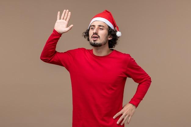 正面図茶色の背景に手を振って若い男休日感情クリスマス
