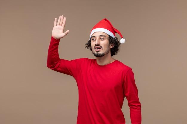 正面図茶色の背景に手を振って若い男クリスマス感情休日