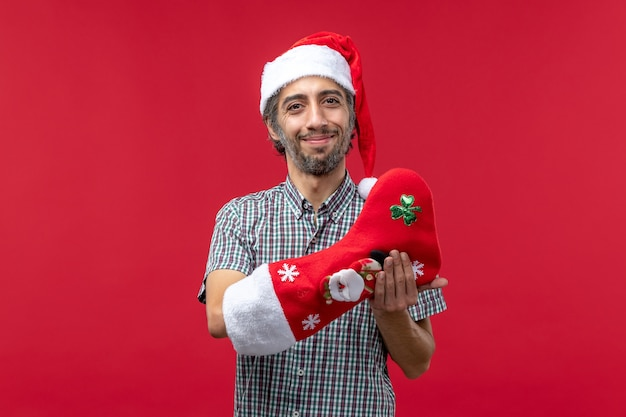 Vista frontale del giovane uomo che indossa il calzino di natale sulla parete rossa