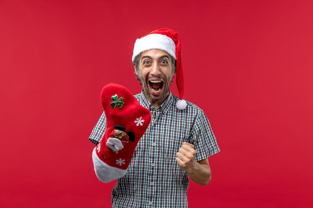 Front view of young man wearing christmas sock on red wall