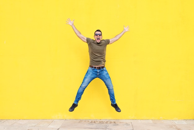 Front view of a young man wearing sunglasses jumping against a yellow bright wall in a sunny day
