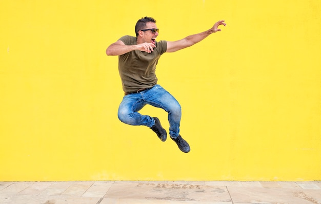 Front view of a young man wearing sunglasses jumping