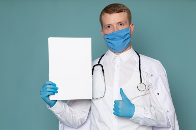 A front view young man in white medical suit blue gloves and mask on the blue desk