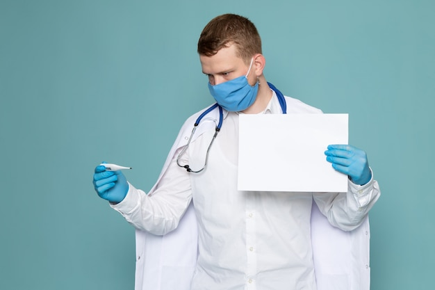 A front view young man in white medical suit using gloves and mask on the blue desk