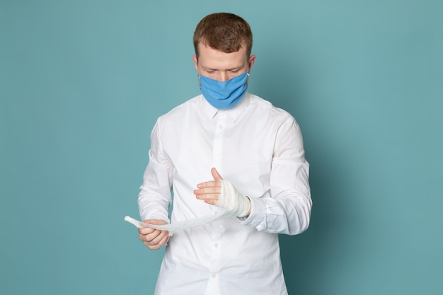 A front view young man in white shirt and blue gloves on the blue space