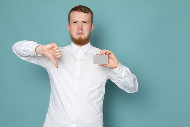 A front view young man in white shirt holding card on the blue space