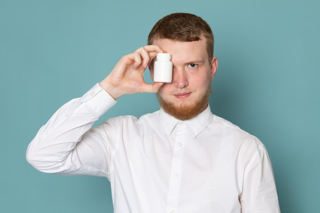 A front view young man in white shirt holding little can on the blue space