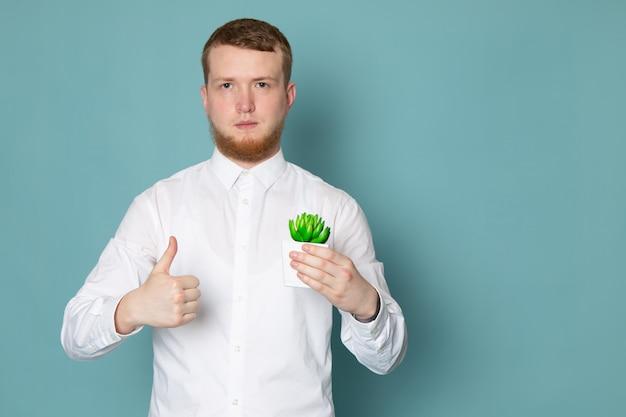 Un giovane di vista frontale in camicia bianca che tiene piccola pianta verde sullo spazio blu