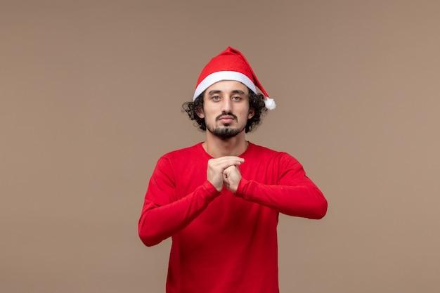 Вид спереди молодой человек с сердитым лицом на коричневом фоне праздничные эмоции рождество
