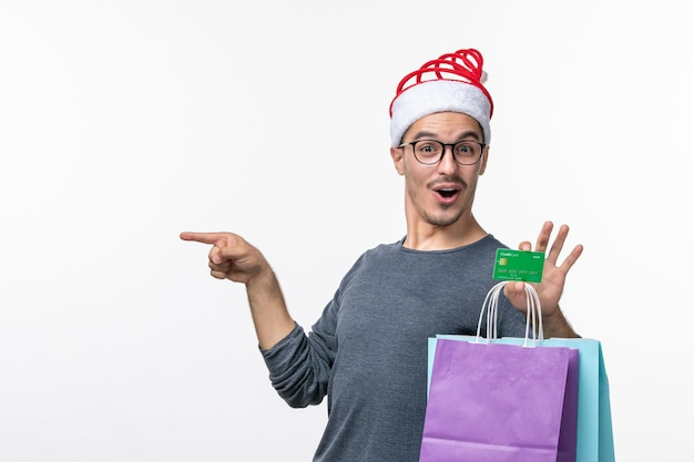 Front view of young man with bank card and packages on white wall
