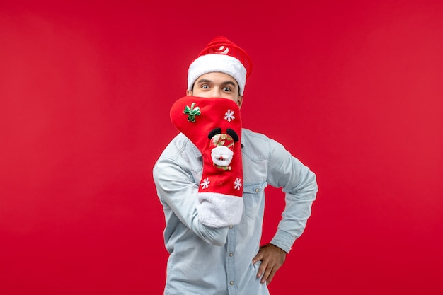 Front view of young man with big christmas sock on red wall
