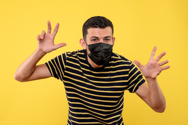 Вид спереди молодой человек в черно-белой полосатой футболке, делая страшный жест на желтом фоне