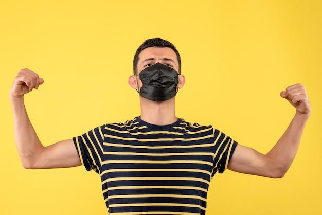 팔 근육 노란색 배경을 보여주는 검은 색과 흰색 줄무늬 티셔츠와 전면보기 젊은 남자