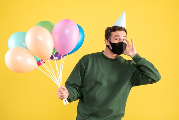 Вид спереди молодой человек с черной маской и разноцветными воздушными шарами, стоящий на желтом