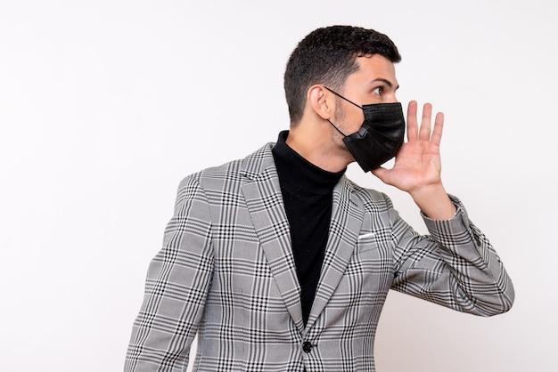 白い孤立した背景に立っている誰かを呼び出す黒いマスクを持つ正面図の若い男