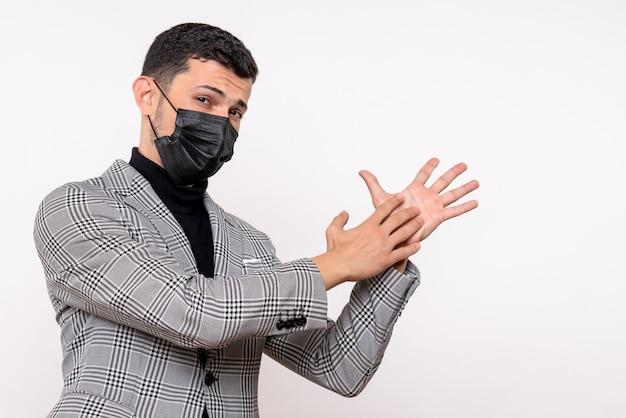 Vista frontale giovane uomo con maschera nera battendo le mani in piedi su sfondo bianco isolato