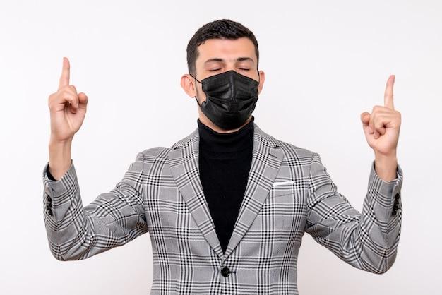 Vista frontale giovane uomo con maschera nera chiudendo gli occhi in piedi su sfondo bianco isolato