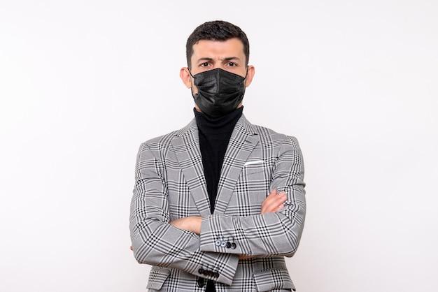 격리 된 흰색 배경에 서 그의 손을 건너 검은 마스크와 전면보기 젊은 남자