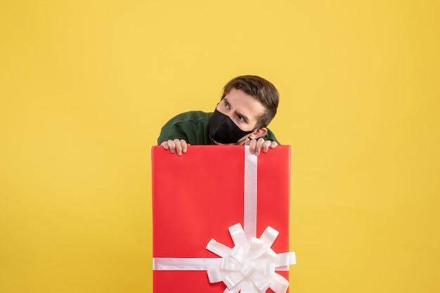 Giovane vista frontale con maschera nera che si nasconde dietro un grande giftbox su giallo