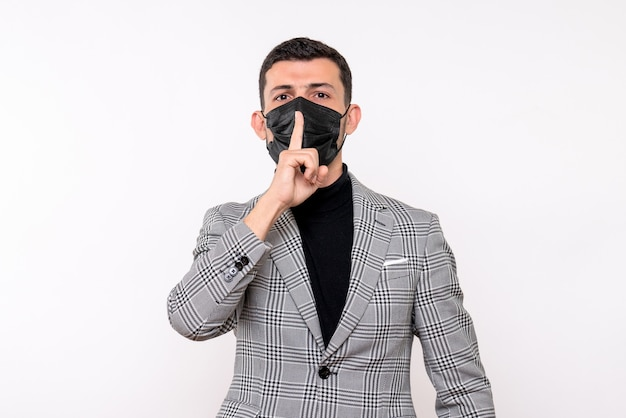 Front view young man with black mask making shh sign standing on white isolated background