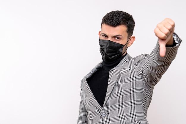 격리 된 흰색 배경 여유 공간에 서 기호 아래로 엄지 손가락을 만드는 검은 마스크와 전면보기 젊은 남자