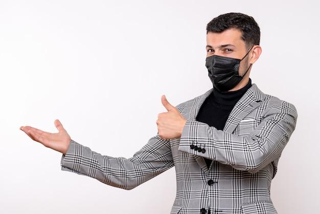 白い孤立した背景に立っているサインアップサインを作る黒いマスクを持つ正面図