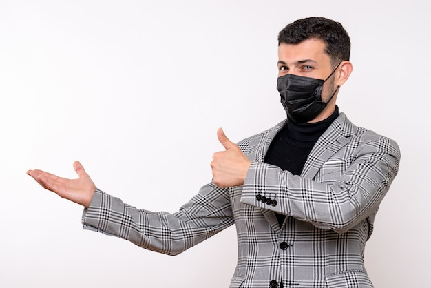 Front view young man with black mask making thumb up sign standing on white isolated background