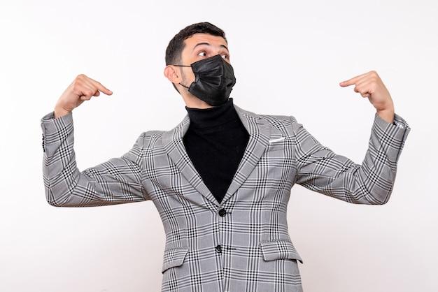白い孤立した背景の上に立っている自分を指している黒いマスクを持つ正面図