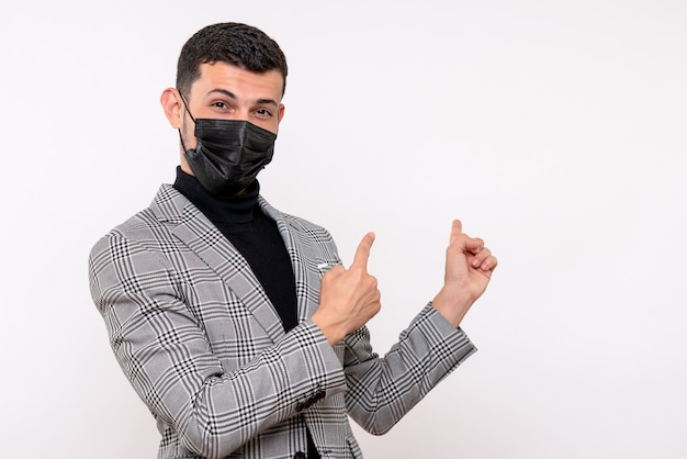 Front view young man with black mask pointing at back standing on white isolated background
