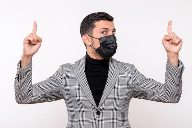 Vista frontale giovane uomo con maschera nera che punta con il dito in alto in piedi su sfondo bianco isolato