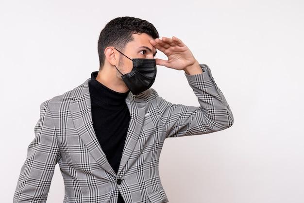 Vista frontale giovane uomo con maschera nera mettendo la mano sulla fronte in piedi su sfondo bianco isolato