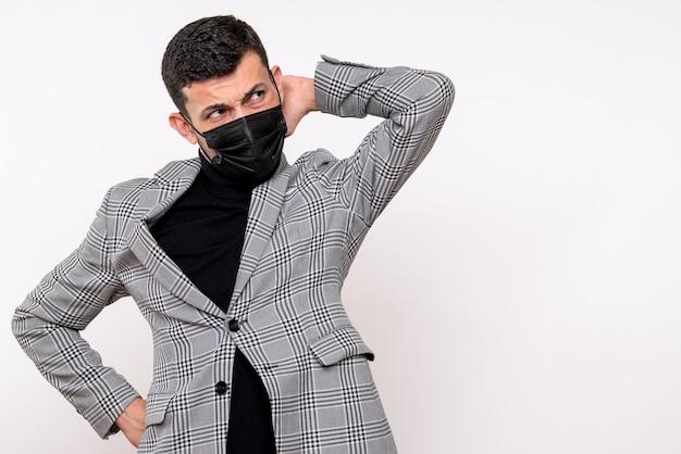 Vista frontale giovane uomo con maschera nera mettendo la mano su un collo in piedi su sfondo bianco isolato