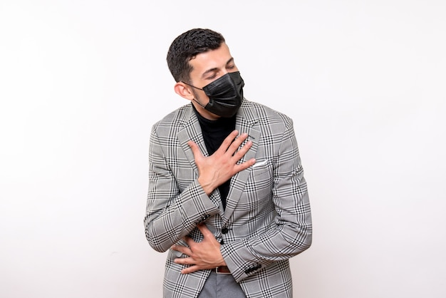 Giovane vista frontale con maschera nera che mette le mani sul petto in piedi su sfondo bianco isolato