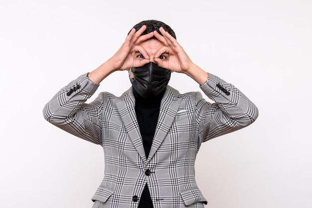 Vista frontale giovane uomo con maschera nera mettendo okey segno davanti ai suoi occhi in piedi su sfondo bianco isolato
