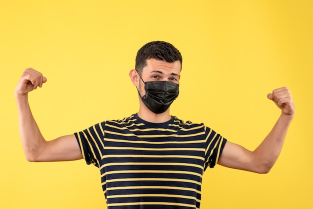 Вид спереди молодой человек с черной маской, показывающий мышцы рук на желтом фоне