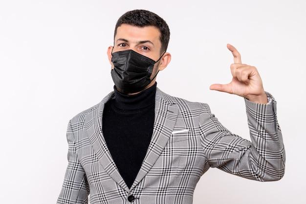 Vista frontale giovane uomo con maschera nera che mostra le dimensioni con le dita in piedi su sfondo bianco isolato