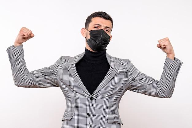 격리 된 흰색 배경에 힘 서 보여주는 검은 마스크와 전면보기 젊은 남자