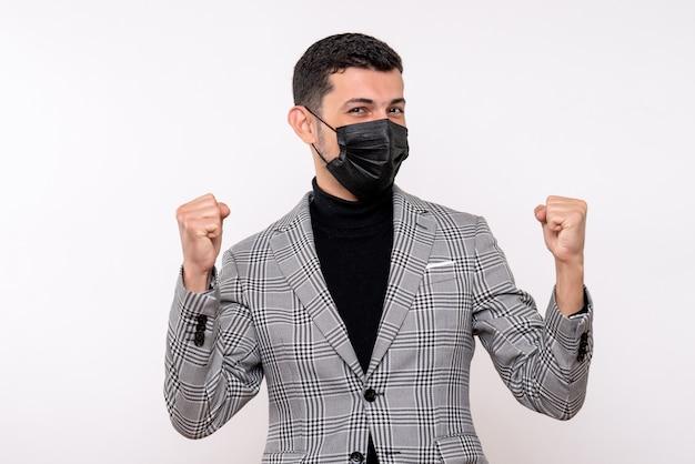 Giovane vista frontale con maschera nera che mostra il gesto vincente in piedi su sfondo bianco isolato