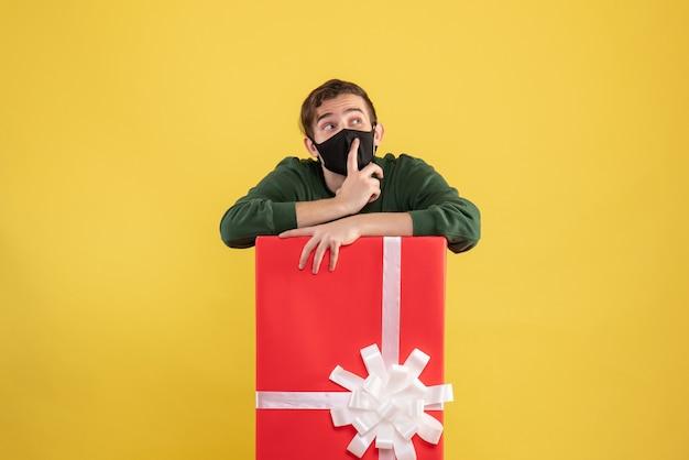 노란색에 큰 giftbox 뒤에 서있는 검은 마스크와 전면보기 젊은 남자