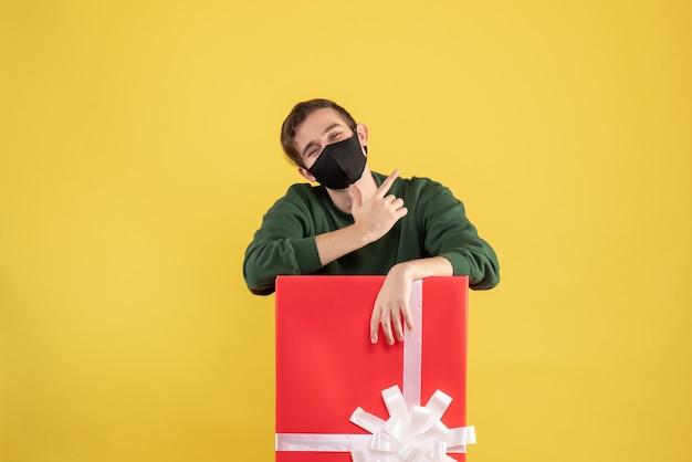Giovane di vista frontale con la maschera nera che sta dietro il grande giftbox su giallo