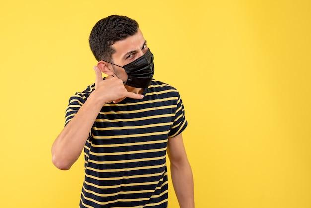 Giovane di vista frontale con la maglietta a strisce in bianco e nero che fa chiamarmi posto libero del fondo giallo del segno del telefono