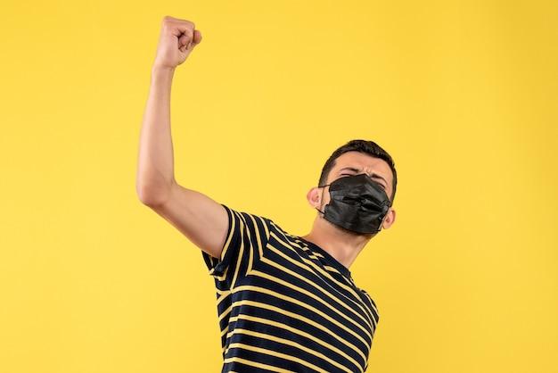 Giovane di vista frontale con la maglietta a strisce in bianco e nero che fa il fondo giallo di gesto vincente