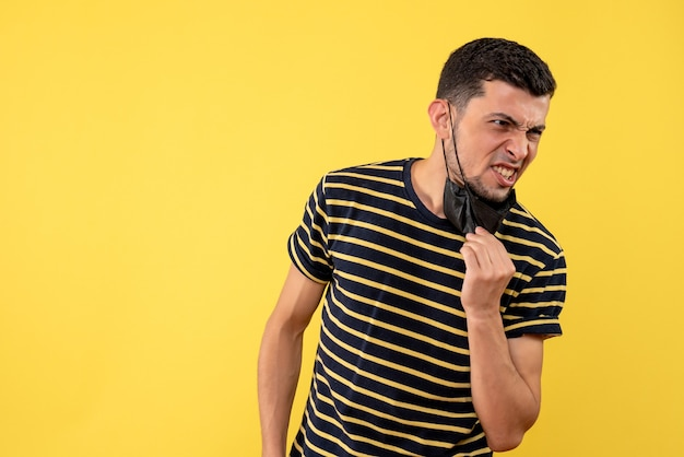 Front view young man with black and white striped t-shirt taking off his mask yellow background copy space